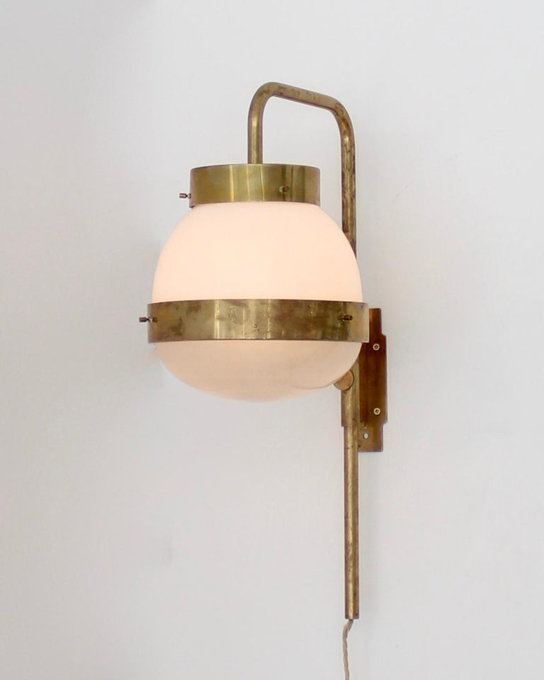 A single Sergio Mazza Italian vintage Delta sconce for Artemide. Brass with Holophane and milk glass encircled by brass bands. Excellent condition.  Rewired for USA.    Measures: 26 in. H x 10 in. W x 14 in. D.