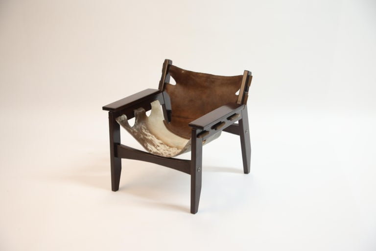 A charming and wonderful example of the 'Kilin' lounge chair by famed Brazilian modern designer Sergio Rodrigues for Oca in 1970s Brazil. Frame is a succulent Brazilian Rosewood and the leather slings are hair-on cowhide. 