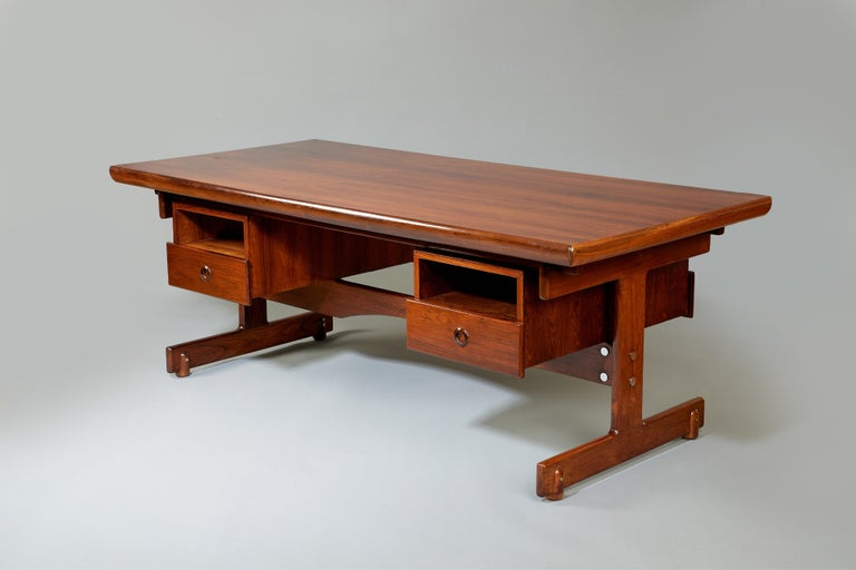 Sérgio Rodrigues (1927–2014)  An important and stately desk, in jacaranda wood with contrasting chrome-plated steel details, by modern Brazilian design pioneer and frequent Oscar Niemeyer collaborator Sérgio Rodrigues. A large floating top, two open