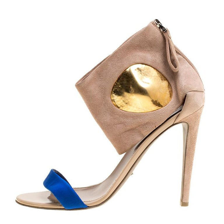You'll leave the crowds amazed when you step out in these stunning sandals from Sergio Rossi. These beige sandals are crafted from suede and featurn an open toe silhouette. They flaunt a blue satin vamp strap and ankle cuffs with gold-tone