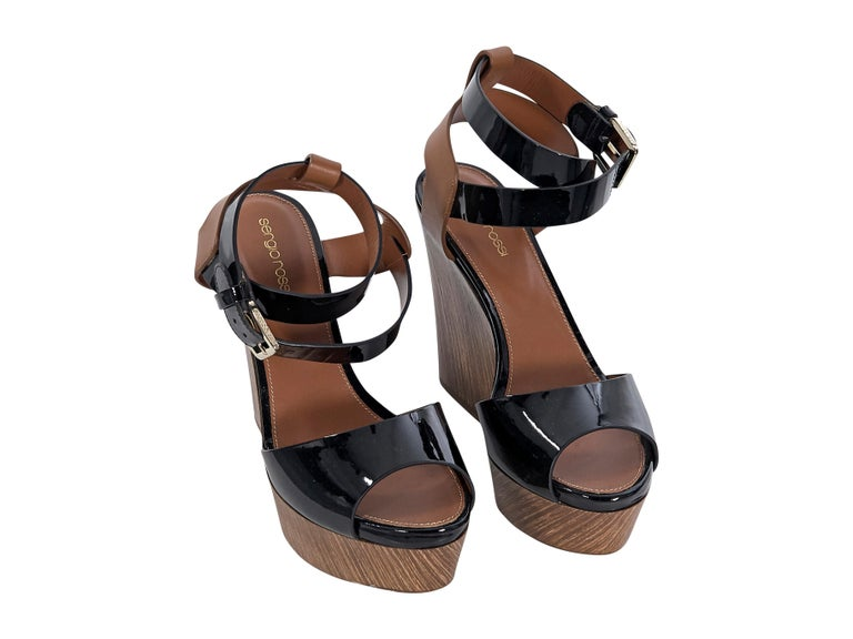 Product details:  Black patent leather and brown leather wedge sandals by Sergio Rossi.  Adjustable ankle strap.  Peep toe.  Wooden notched wedge design.   Condition: Pre-owned. Very good. Est. Retail $ 750.00