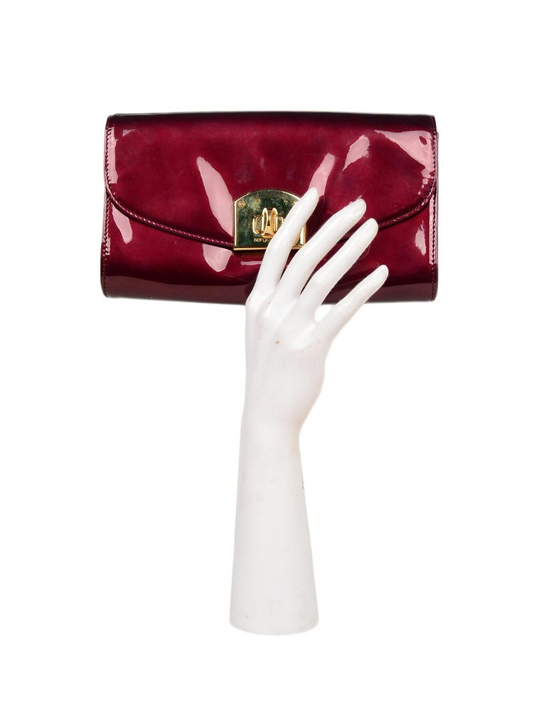 Sergio Rossi Burgundy Patent Leather Clutch W/ Wrist Strap  Made In: Italy Color: Burgundy, gold Hardware: Goldtone Materials: Patent leather, metal Lining: Tan leather Closure/Opening: Flap top with twistlock closure  Exterior Pockets: