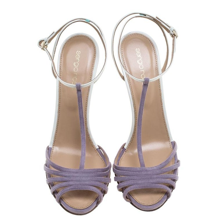 This amazing pair of sandals is from Sergio Rossi. They have been crafted from suede with purple-coloured strappy vamps. The open toe sandals come with white leather T-straps featuring adjustable ankle fastenings, comfortable insoles, and 11.5 cm