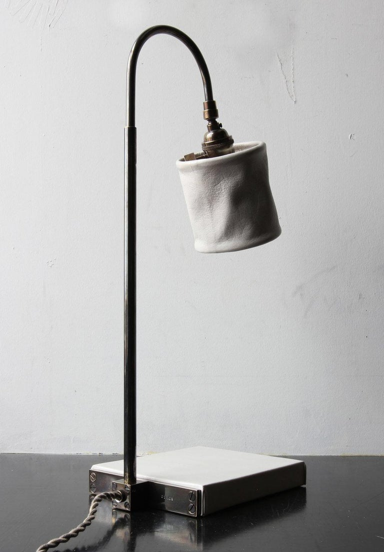 Solid machined brass in dark patinated brass finish, hand-dyed and waxed leather wrapped wood, soft unstructured pivoting leather shade, hand-dyed braided cotton cord. All material finishes are living finishes: they will change and patina for the