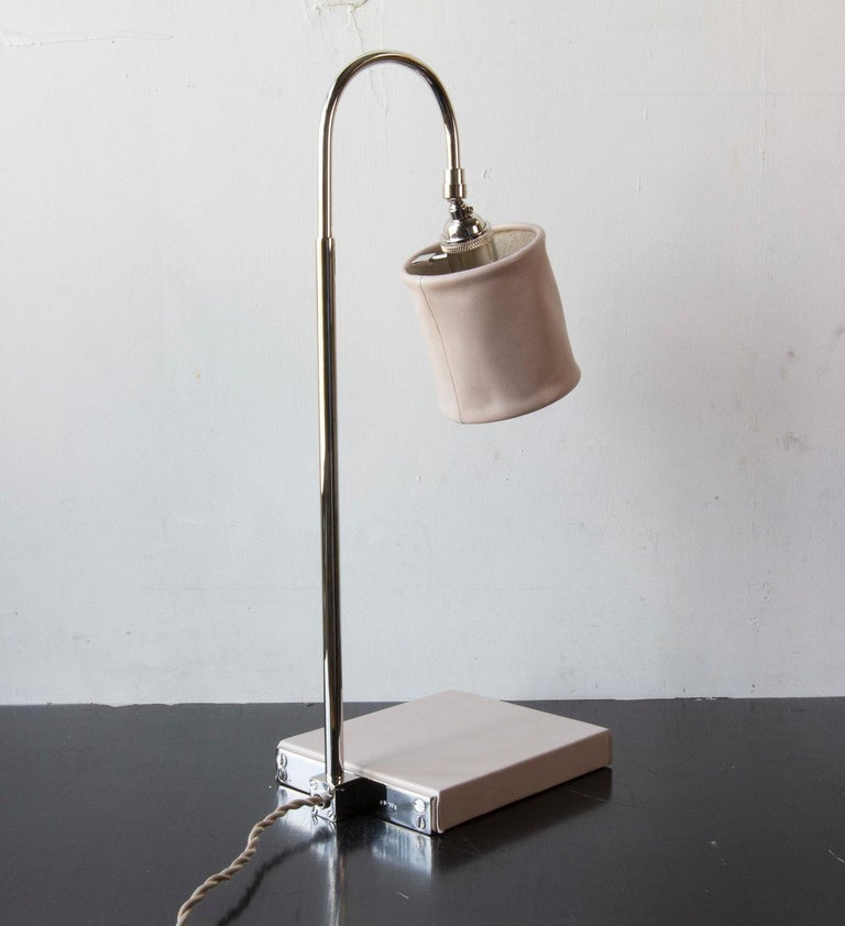 Solid machined brass in polished nickel-plated finish, hand-dyed and waxed leather wrapped wood, soft unstructured pivoting leather shade, hand-dyed braided cotton cord. All material finishes are living finishes: they will change and patina for the