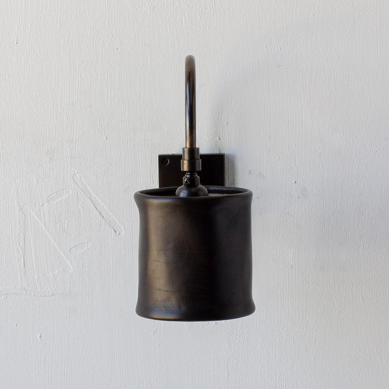 Solid machined brass in dark patinated finish, hand-dyed soft unstructured leather pivoting shade. All material finishes are living finishes: they will change and patina for the better with time and use. Backplate is made to fit only a single gang