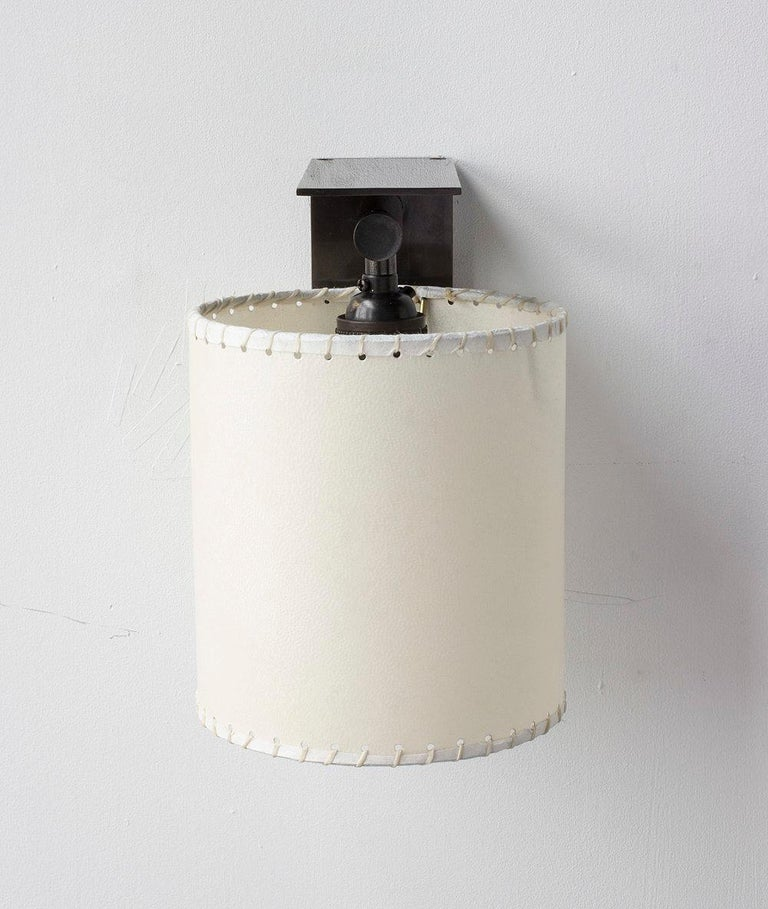 Solid machined dark patinated brass, hand-stitched goatskin parchment shade. All material finishes are living finishes: they will change and patina for the better with time and use. Goatskin parchment is a excellent diffuser of light and is