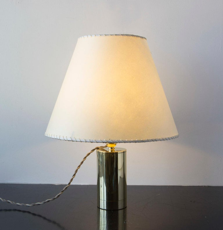 Solid machined polished unlacquered brass, handstitched goatskin parchment shade, with hand-dyed braided cotton cord. All material finishes are living finishes: they will change and patina for the better with time and use. Goatskin parchment is a