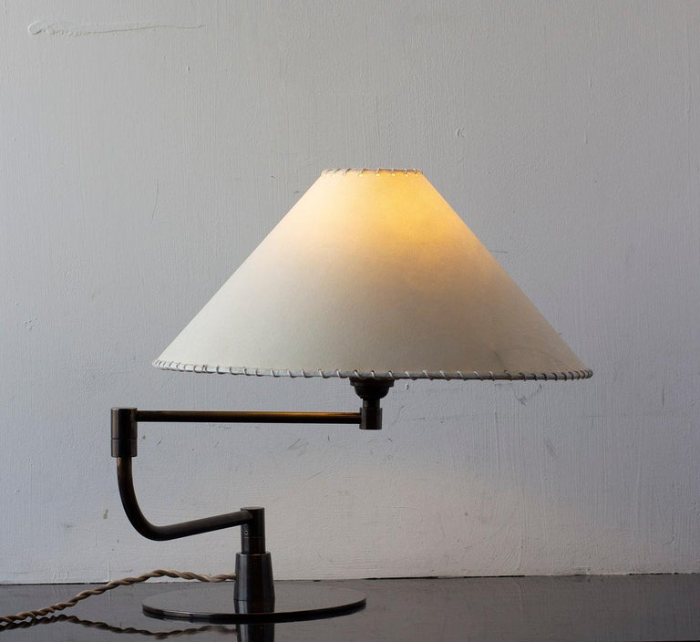Solid machined brass and goatskin parchment shade with hand-dyed braided cotton cord. Adjustable pivot arm. Goatskin parchment is a excellent diffuser of light and is naturally figured and textured, similar to the surface of the moon. All material