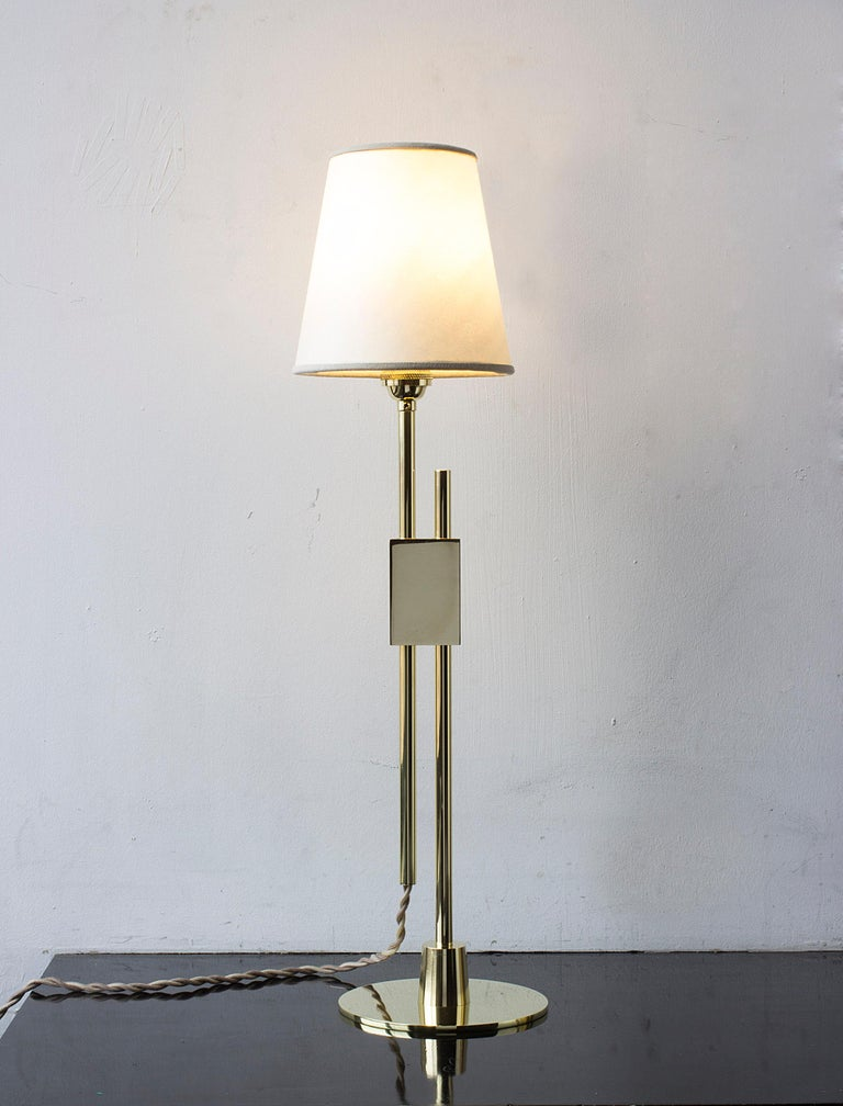 Solid machined polished unlacquered brass, goatskin parchment shade with ultra-suede trim, hand-dyed braided cotton cord. Adjustable height from 24