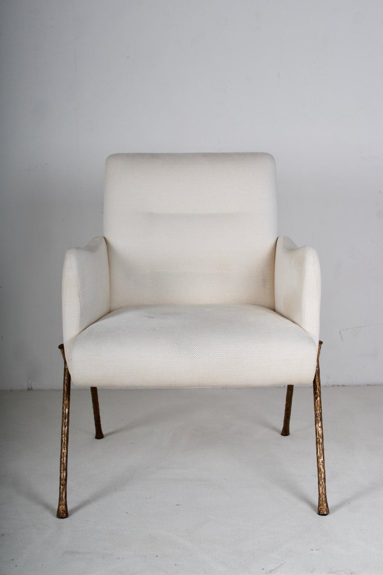 A very lovely armchair fully upholstered, legs in hammered bronze. The linen blend fabric is slightly soiled but in great condition.  There are three chairs available.