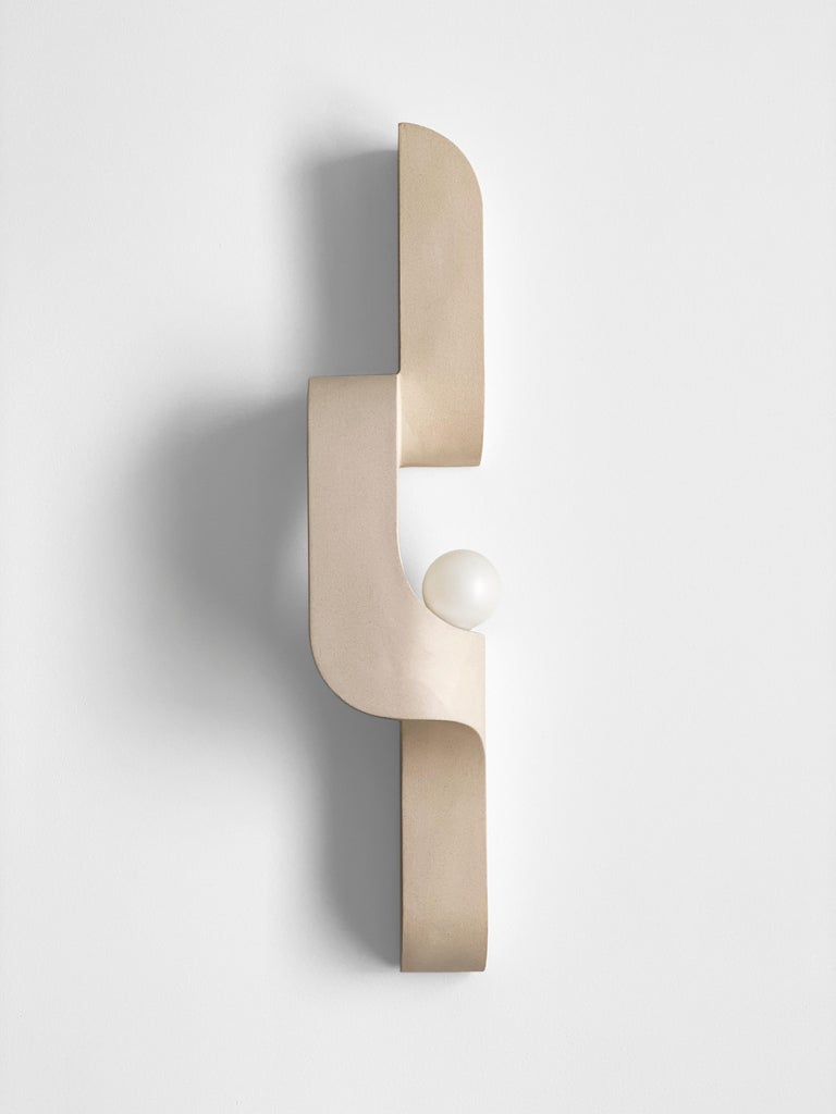 In this sandy slipcast ceramic wall sconce, generous curves are paired with crisp edges and the repetition of geometry to create a flow. The sconce snakes up and off the wall, a sculptural lighting piece that's understated, and almost