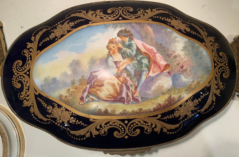 A background of dark cobalt blue with gilding details of scrolls and dots alternated with roses and foliage decorate this vanity box. The dome aspect of the lid features a hand painted romantic pastoral scene of a couple signed by B. Tre'haut. The