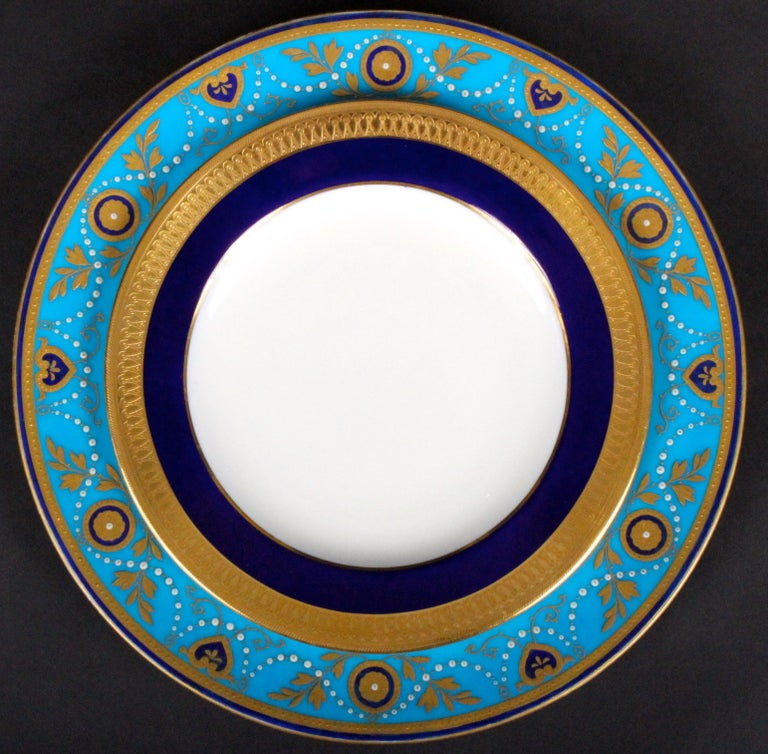 This is a set of 12 armorial-ware 22-karat gold encrusted and raised-paste gold porcelain dinner or service plates, with 12 coordinating plates. They were made by Minton, Stoke-on-Trent, England. The plates feature Minton's most popular color,