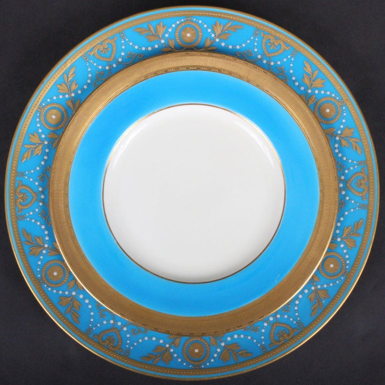 This is a set of 12 monogrammed 22-karat gold encrusted and raised-paste gold turquoise porcelain dinner or service plates, with 12 coordinating turquoise plates. They were made by Minton, Stoke-on-Trent, England. The plates feature Minton's most