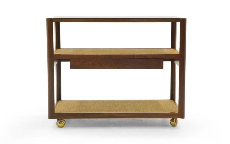 Edward Wormley for Dunbar serving cart or bar trolley with drawer on brass casters. Beautiful mix of materials: Sculpted Brazilian rosewood frame (see details in photos), shelves are cork covered, and the black slate top has been polished to virtual