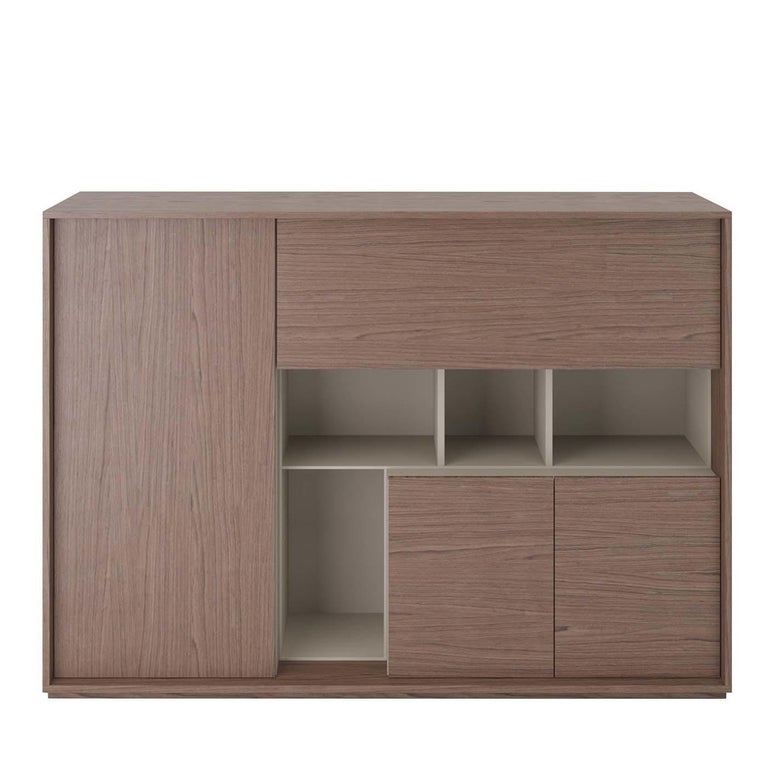 This elegant and versatile sideboard boasts an ingenious, durable silhouette made of heat-treated, durmast-veneered wood with inserts and internal structure in gray-finished melamine. From left to right, the piece comprises a door with a