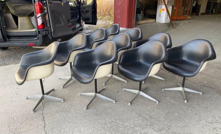 Set of 10 Charles and Ray Eames padded arm shell swivel chairs, Herman Miller/ alum star base, featuring white fiberglass shells, black padded upholstery, aluminum 4-star bases, nice original condition, minor blemishes to black Naugahyde, Classic