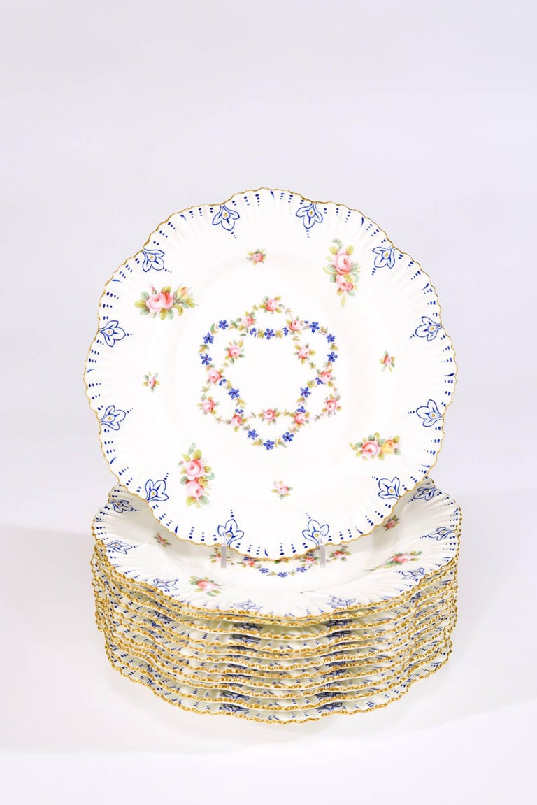 This set of 12 dinner plates were made by Coalport in 1889 and retailed by Gilman Collamore, New York. Evoking the colors and style of Sevres porcelain, they have shaped rims with molded relief and trimmed in gold. Hand-painted roses and