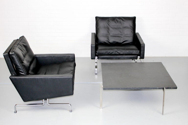 Set of two PK 31 easy chairs and matching PK61 coffee table. Dull chromium plated steel table with top of black slate. Easy chairs with new high quality black leather (Elmosoft) and frame in matte chromed steel. The frame of the chairs is marked.