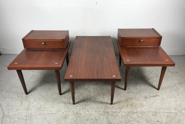 A set of 3 vintage tables manufactured by American of Martinsville. Step ends, one drawer on each with brushed aluminum pulls and the top features X-shaped ornamental inlays in brushed aluminum. Matching coffee / cocktail table, Classic modernist