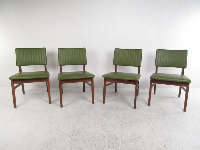 Stylish set of four Mid-Century Modern dining chairs made by the American manufacturer B.L. Marble Furniture Company. Angular solid wood frames with seats and backrests covered in a green faux-leather upholstery. Sure to be a great addition to any