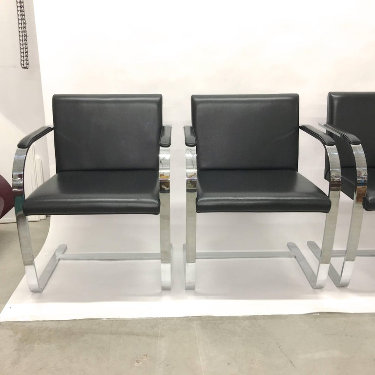 Set of four Brno chairs with flat bar polished chromed steel cantilevered frame and black leather upholstered seats and arm pads.  These were produced by Knoll in 2005 and appear to have been barely used at all.  Excellent condition.  Arm
