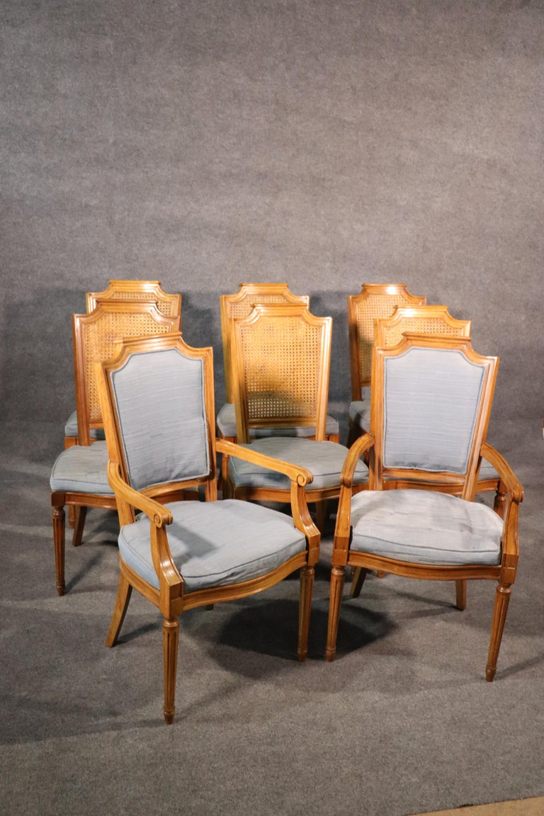 This is a clean set of American-made French style chairs, circa 1950. They each feature undamaged cane backs and beautiful light walnut frames and are in good original condition with blue linen upholstery.  The armchairs measure 38 tall x 21 wide