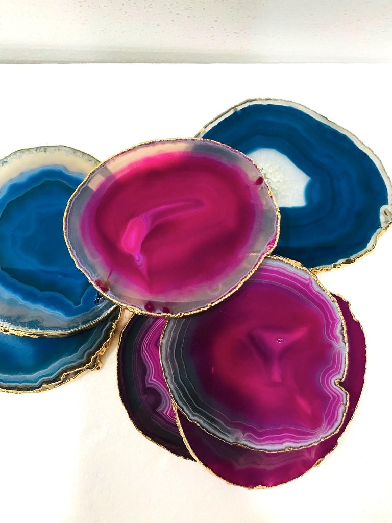 Set of eight organic modern agate and crystal coasters with 24-karat gold-plate finish. Set includes four fuschia and four turquoise coasters with polished fronts and natural edges. Make beautiful and unique accessories to any coffee table or
