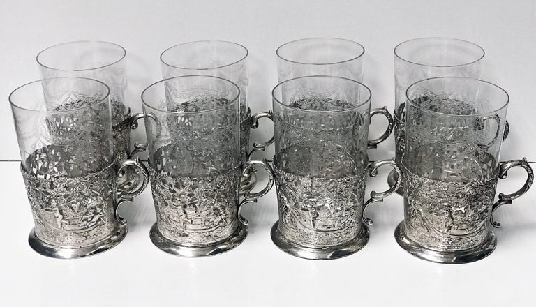 Set of 8 silver glass tea holders, Germany, circa 1900. Each of 0.935 standard silver, depicting beautifully scenes of cherubs, putti and angels amidst foliage. Each glass insert with festoon engraved foliate decoration. Measures: Height 4.50