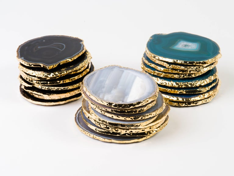Stunning natural agate and crystal coasters with 24-karat gold-plated edges. Polished fronts and natural rough edges. No two pieces are alike. Make beautiful accessories to any coffee table or dining table setting. Three color variations are