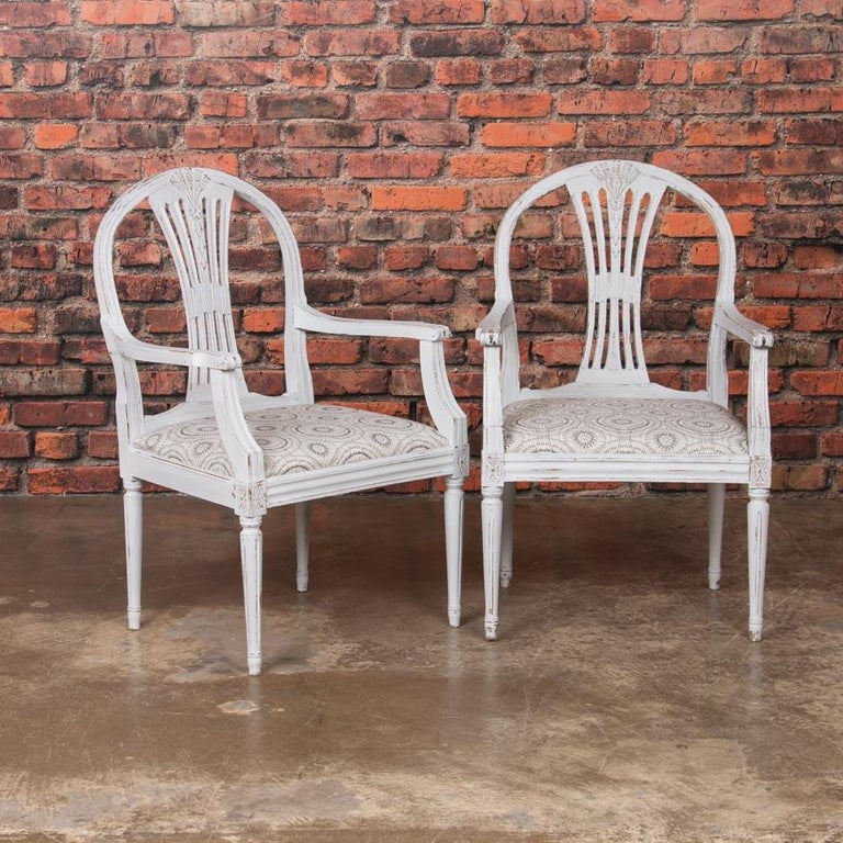 Timeless and romantic, this set of 10 Swedish chairs have a lovely light gray, slightly distressed paint which creates an alluring contrast with the hardwood beneath. This soft color of pale gray, (almost white) paint beautifully accentuates the