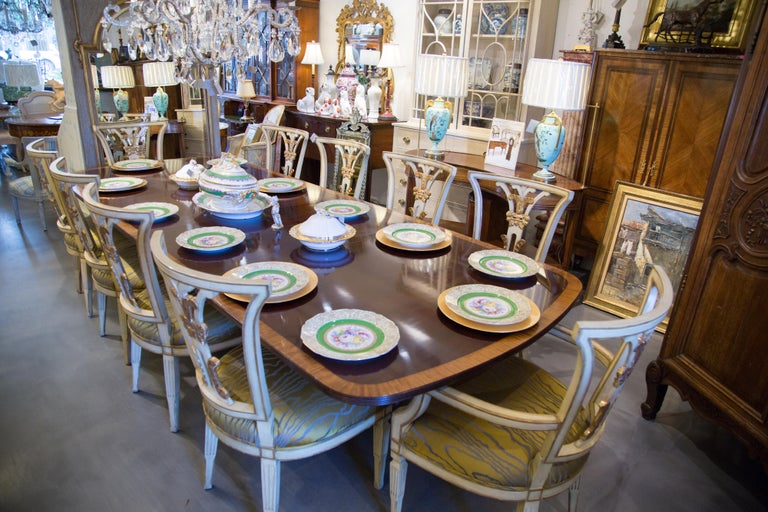 This is a sophisticated set of 10 cream painted and parcel gilt dining chairs. The chairs includes two arm and eight side chairs. The chairs have slightly concave backs, centred by a plume-like back slat over a fully padded seat. The chairs are