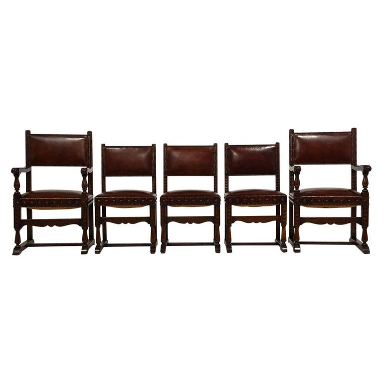 This set of ten 1900s Antique Baroque-style dining chairs feature solid oak wood frames with the original dark walnut color finish. The frames are adorned with carved accents and turned wood arms and legs. The chair seat and back are upholstered in