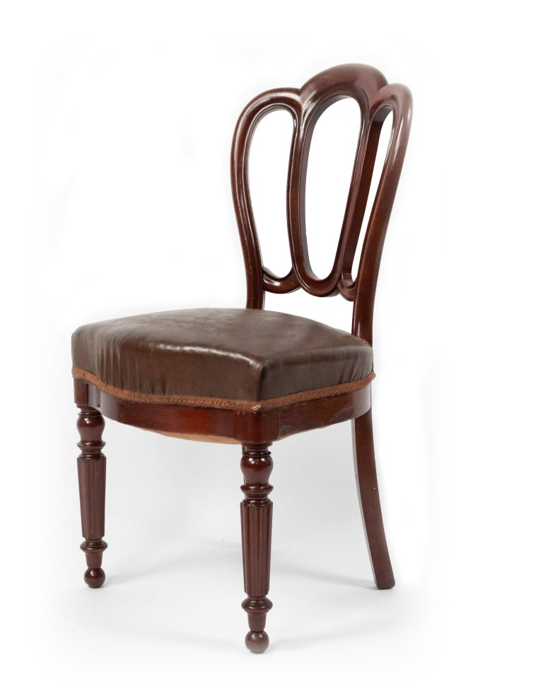 Set of 10 French Victorian (late 19th century) mahogany side / dining chairs with shaped open backs, leather seats, and fluted front legs.
