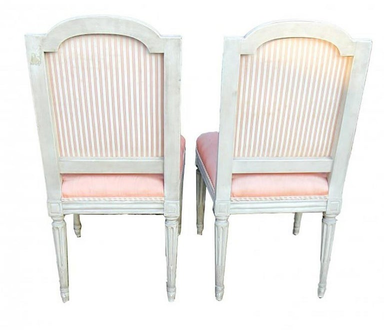Great set of 10 French Louis XVI style carved and painted side chairs. Upholstered in a pink fabric. Note: There are some stains on the fabric, but the overall condition of the chairs is good. Very nice!!