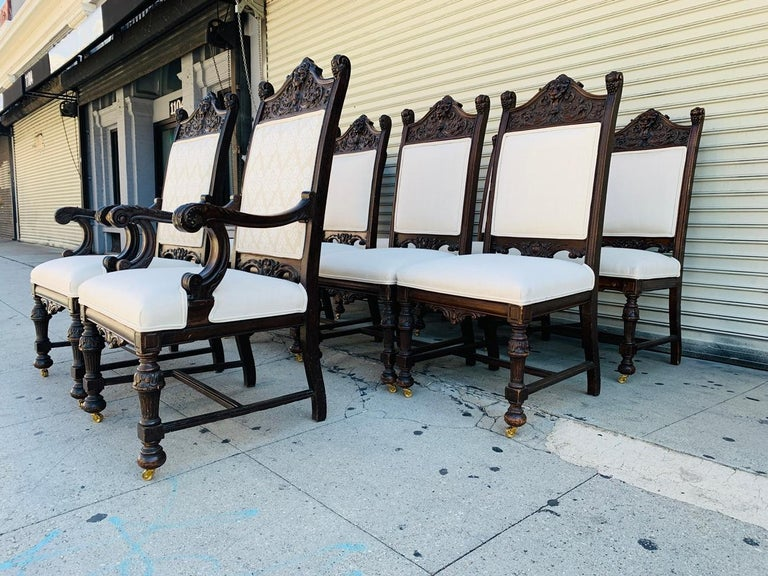 Beautiful set of 10 high back chairs from the early 1900s, the frames are made out of solid wood and heavily carved, the set consist of 8 side chairs and 2 armchairs. The pieces were reupholstered by Castle Interiors Decorating of Brooklyn NY for