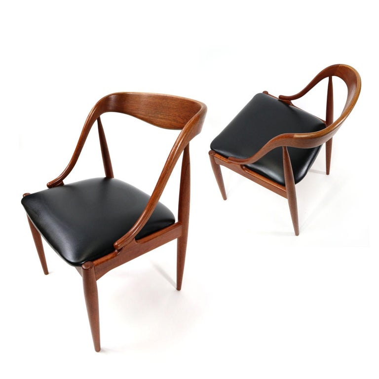 Absolutely exquisite set Mid-Century Modern Danish teak dining chairs. This set of 10 chairs was designed by Johannes Andersen for Uldum Møbelfabrik. The chairs are labeled beneath the seat. You don't have to be a furniture pro to see how special