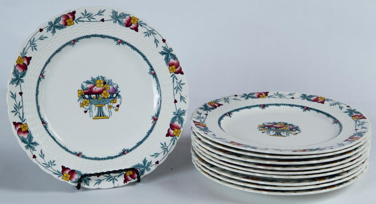Set of 10 Minton's Stanhope plates, England, circa 1900. The Stanhope pattern features a fruit and floral border and center design with a blue and gold palette. There is a raised basket weave detail and scalloped rim. Minton's mark.