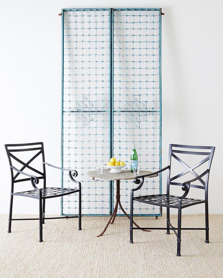 Large set of 10 aluminum garden patio chairs or dining chairs made in the neoclassical taste. Featuring a square back and scrolled arms. The seat has a decorative woven design and the chairs are finished in matte black. X form motif on the backs and