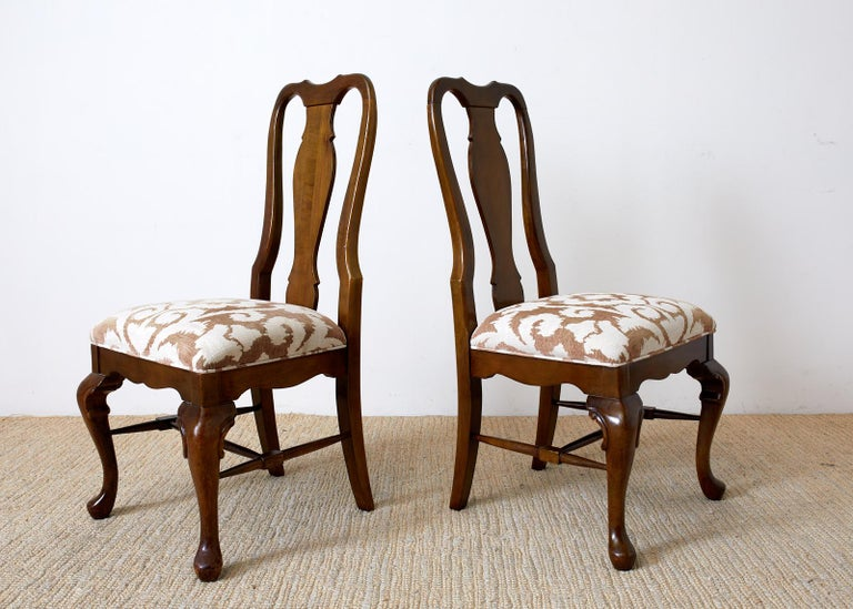Handsome set of ten mahogany dining chairs made in the Queen Anne taste. Features a tall shaped back having a vasiform splat with an upholstered seat. Modern floral motif print on linen style fabric seat. Supported by cabriole legs in front ending