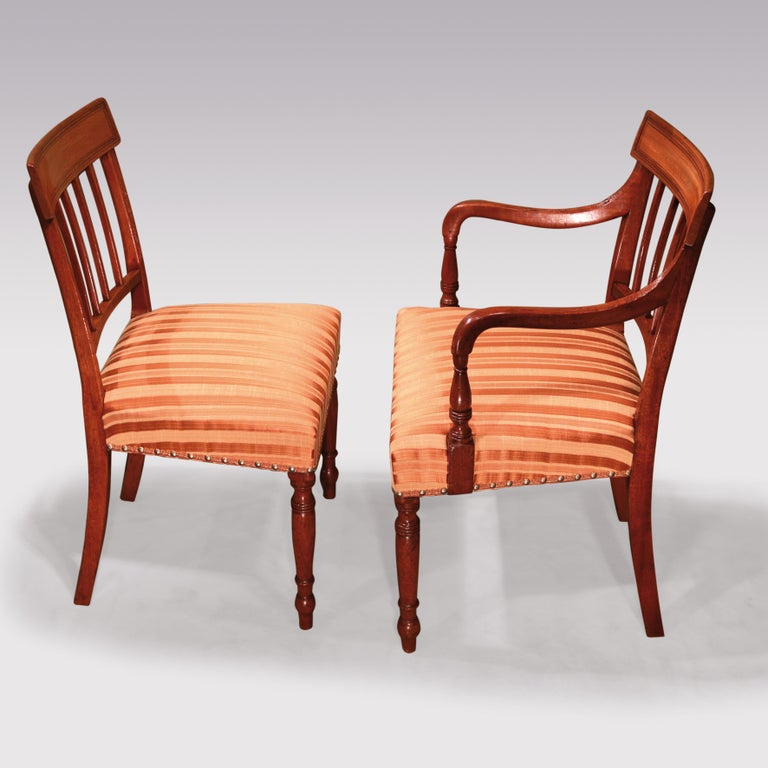 A set of 10 single and two-arm Regency period mahogany dining chairs, having paneled curved tops above reeded splats. The chairs with stuffover seats supported on ring-turned tapering legs. (An armchair's leg repaired).