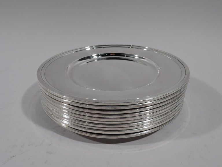 Set of 10 modern sterling silver bread and butter plates. Made by Tiffany & Co. in New York, circa 1923. Each: Deep well and molded rim. Fully marked. All have pattern no. 20198 (first produced in 1923). Eight have director's letter m (1907-47) and