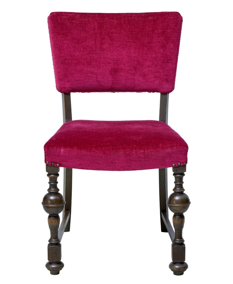Striking set of 12 near pink upholstered dining chairs, circa 1920.  Later covered in a cerise pink faux velvet covering. Shaped backs and over stuffed seats. Turned front legs united by stretcher to the back tapering leg.  Expected wear and