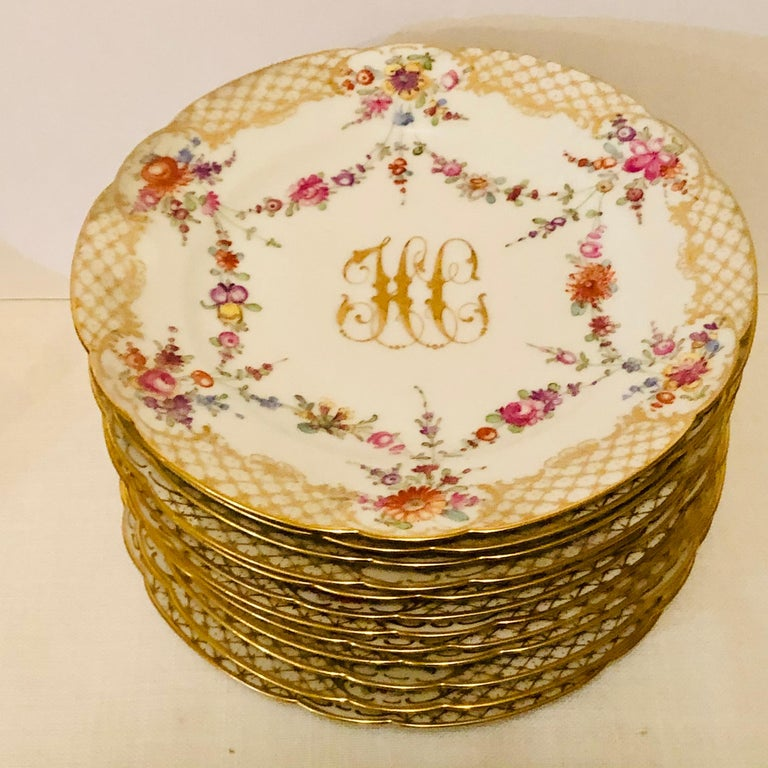 This is a lovely set of twelve Ambrosius Lamm dessert plates. Each plate is painted with different flowers. There is a central raised gold monogram, which is surrounded by a ribbon of flowers. The plates have a border of cross hatched gold and white
