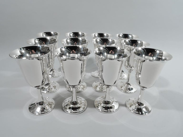 Set of 12 Modern sterling silver goblets. Made by Wallace in Wallingford, Conn. Each: Bell-form bowl with upward tapering stem and round and raised foot. A classic design that make's any occasion special. Fully marked including maker's stamp and no.