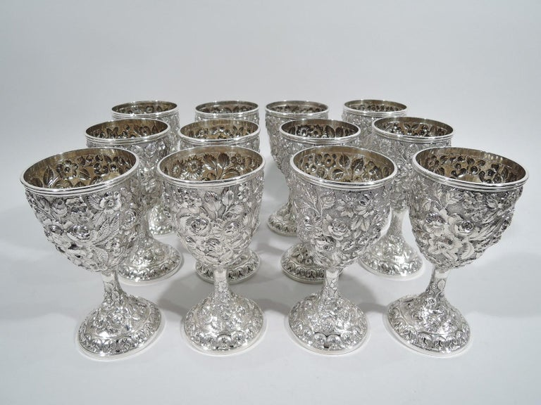 Set of 12 turn-of-the-century sterling silver goblets. Each: Oval bowl on cylindrical support flowing into raised foot. Floral and foliate repousse on stippled ground. Bowl has plain cartouche (vacant) in scrolled frame. Interior gilt washed. Pretty
