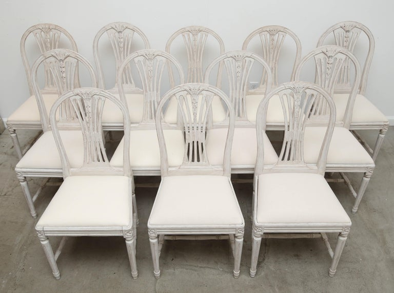 Set of 12 antique Swedish painted Gustavian style dining chairs, each with arched backs carved with wheat and bell flowers, openwork spelt, square drop-in seats, round fluted legs, joined by H-shaped stretchers, and carved rosettes on top of seat