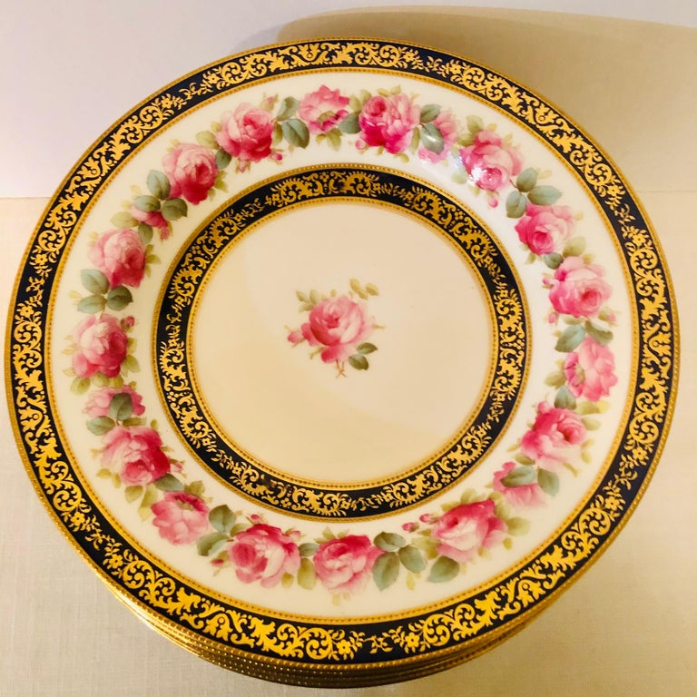 This is a stunning set of twelve Cauldon English wide rim soup bowls. They are decorated with a central pink rose with a ring of beautiful pink roses on their inner border. The central rose and the ring of roses are each surrounded by a cobalt