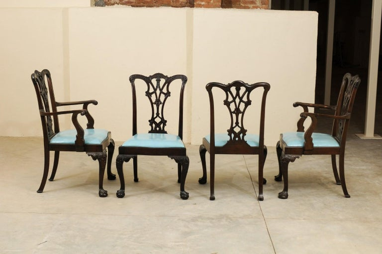 The Chippendale style mahogany dining chairs with 2 arm chairs and 10 side chairs featuring pierced black splats, removable light blue leather seats and carved cabriole legs with ball and claw feet.   Arms dimensions are 41